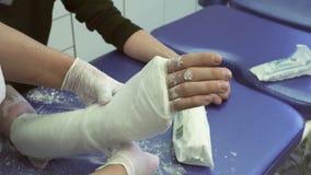 O doutor envolve a atadura em torno do braço ferido que descansa no sofá macio video estoque