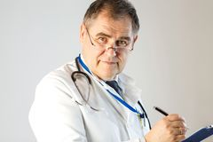 O doutor escreve uma prescrição e olhares na cara fotos de stock