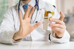 O doutor está advertindo contra cigarros de fumo e está dando o conselho para parar fumar imagens de stock royalty free