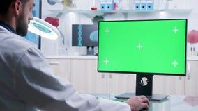 O doutor está datilografando no teclado de computador com tela verde vídeos de arquivo