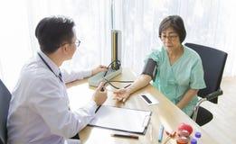 O doutor está examinando o paciente idoso da mulher que usa um estetoscópio imagem de stock