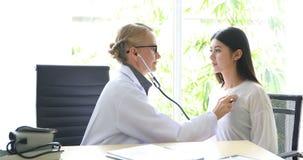 O doutor está explicando sobre os resultados do raio X do cérebro à mulher imagens de stock
