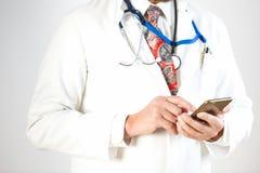 O doutor está guardando um smartphone em um caso, fundo branco fotos de stock