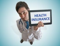 O doutor está mostrando a tabuleta com o texto do seguro de saúde escrito fotografia de stock