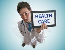 O doutor está mostrando a tabuleta com o texto dos cuidados médicos escrito Vista da parte superior imagens de stock royalty free