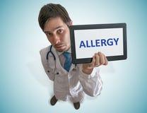 O doutor está mostrando a tabuleta e o aviso contra a alergia Vista da parte superior fotografia de stock