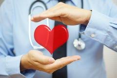 O doutor está protegendo o coração com mãos Cuidados médicos e Cardiov Imagens de Stock