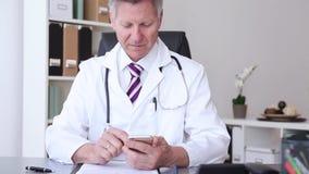 O doutor está usando o telefone esperto video estoque