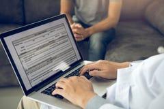 O doutor está usando um portátil ao datilografar o registro de história pessoal paciente e ao dar o conselho sobre o tratamento p fotos de stock