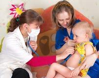 O doutor examina a criança Fotos de Stock