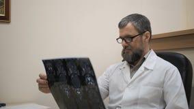 O doutor examina o MRI do c?rebro do paciente filme