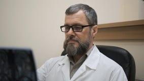 O doutor examina o MRI do c?rebro do paciente video estoque