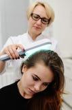 O doutor examina o escalpe um dispositivo especial com uma lâmpada UV fotos de stock