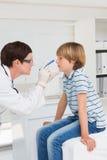 O doutor examina o rapaz pequeno com uma luz Foto de Stock