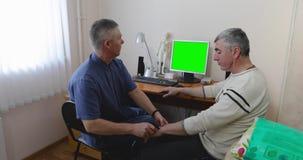 O doutor examina o paciente que usa um computador filme