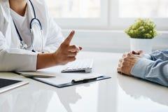 O doutor fêmea adverte seu paciente com um dedo aumentado foto de stock