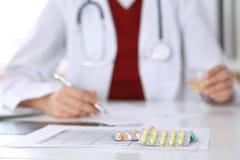 O doutor fêmea da medicina enche acima o formulário da prescrição ao close up paciente A panaceia e a vida salvar, prescrevem o t Imagens de Stock
