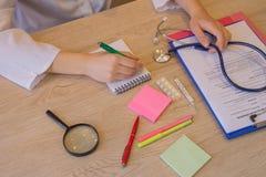 O doutor fêmea da medicina entrega o formulário médico paciente de enchimento Médico que trabalha com papel na sala do escritório Imagens de Stock Royalty Free