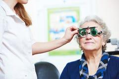 O doutor fêmea examina a vista superior do olho da mulher com phoropter Imagem de Stock