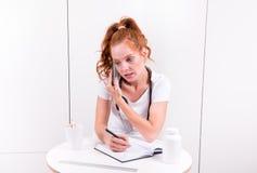 O doutor fêmea novo está tomando notas durante um telefonema imagem de stock