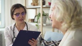 O doutor fêmea novo no uniforme e nos vidros está fazendo notável e está falando com paciente video estoque