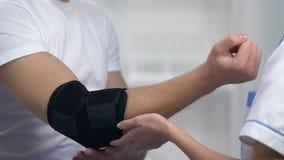 O doutor fêmea que aplica a ortose acolchoada cotovelo, diminui sintomas da dor da artrite vídeos de arquivo