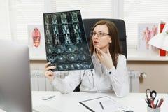 O doutor fêmea que senta-se na mesa com computador, filme radiografa o cérebro pelo mri radiográfico da varredura do ct da imagem imagem de stock