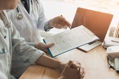 O doutor fêmea seguro revê a informação médica paciente e imagem de stock royalty free