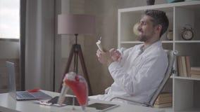 O doutor farpado bem sucedido, satisfeito feliz dispersa os dólares que sentam-se em uma cadeira em uma tabela de trabalho na clí video estoque