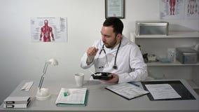 O doutor farpado bloqueou durante ter um almoço em seu escritório Ele que come do recipiente plástico da cesta de comida, bebendo video estoque