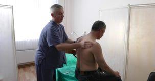 O doutor faz massagens ao homem em um escritório video estoque