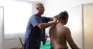O doutor faz uma massagem ao paciente no escritório vídeos de arquivo