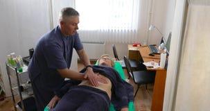O doutor faz uma massagem do abdômen paciente do ` s vídeos de arquivo