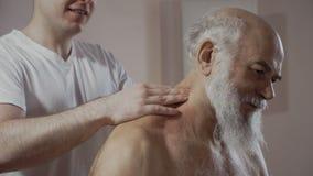 O doutor faz uma massagem terapêutica dos ombros ao homem superior video estoque