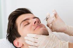 O doutor Giving Injection On enfrenta do homem Imagens de Stock Royalty Free