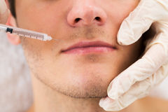 O doutor Giving Injection On enfrenta do homem Imagem de Stock