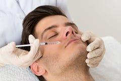 O doutor Giving Injection On enfrenta do homem Fotos de Stock Royalty Free