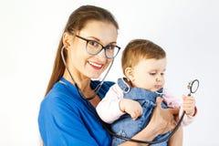 O doutor guarda a criança em seus braços e os sorrisos, a criança tocam no estetoscópio imagens de stock