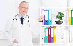 O doutor guarda um cartão em seu escritório fotos de stock