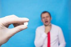 O doutor guarda um comprimido antisséptico em sua mão para uma garganta inflamada, no fundo um homem cuja a garganta inflamada te foto de stock