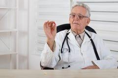 O doutor idoso com vidros estuda o comprimido vermelho Fotos de Stock Royalty Free