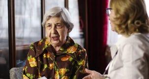 O doutor idoso da mulher ri com a avó durante a recepção e o exame vídeos de arquivo