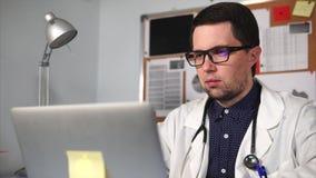 O doutor imprime o texto no portátil em seu escritório privado na clínica video estoque