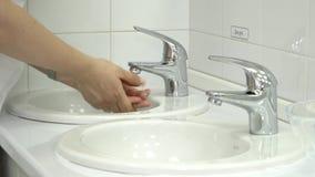 O doutor lava com cuidado suas mãos sob a água da torneira filme