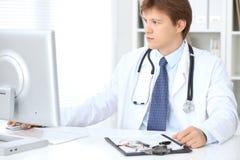 O doutor masculino amigável está sentando-se na tabela e está trabalhando-se no escritório do hospital Apronte para examinar e aj Fotos de Stock