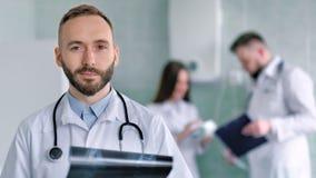 O doutor masculino caucasiano com barba e o estetoscópio no laboratório branco revestem guardar o instantâneo do raio X filme