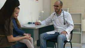O doutor masculino de sorriso que fala com a menina tímida que senta-se em seu ` s da mãe dobra video estoque