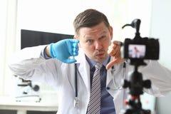 O doutor masculino do vlogger olha a câmera fotografia de stock