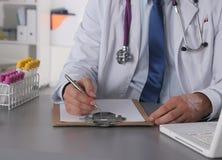 O doutor masculino escreve na mesa com tubo de ensaio Fotografia de Stock Royalty Free