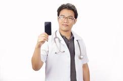 O doutor masculino no revestimento branco está usando um smartp moderno fotografia de stock